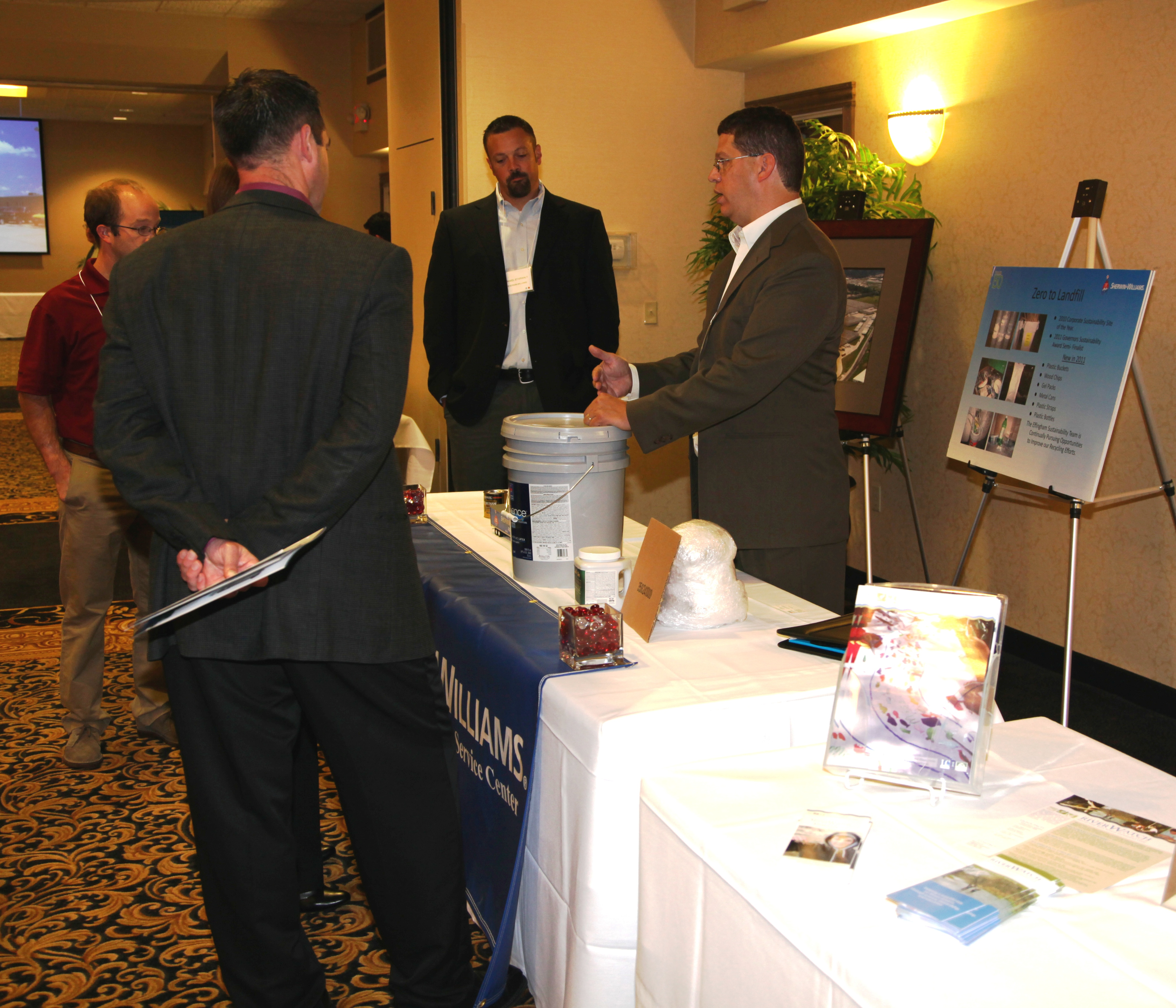An exhibitor discusses his display with other participants