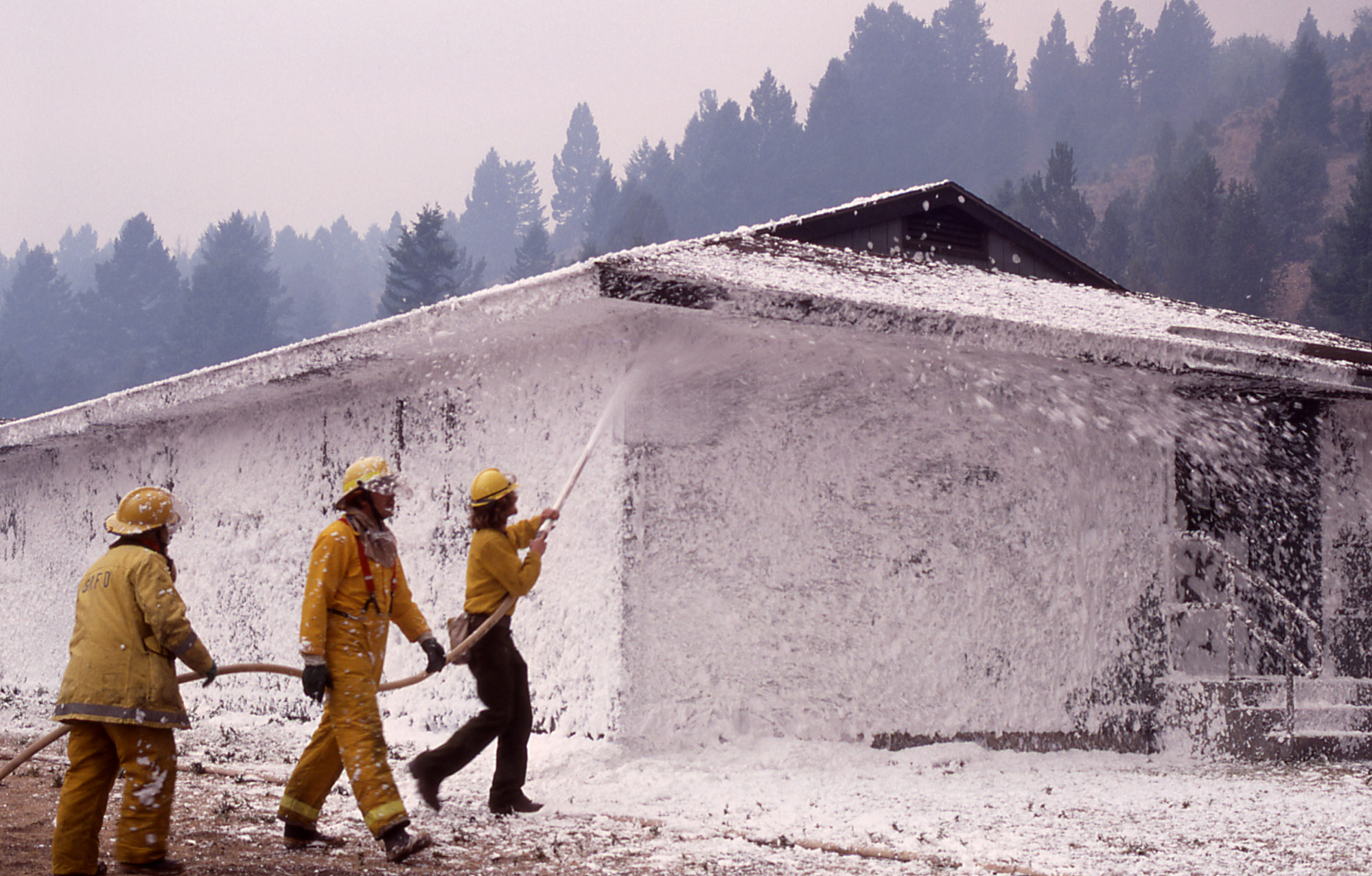 firefighters spraying foam on a building