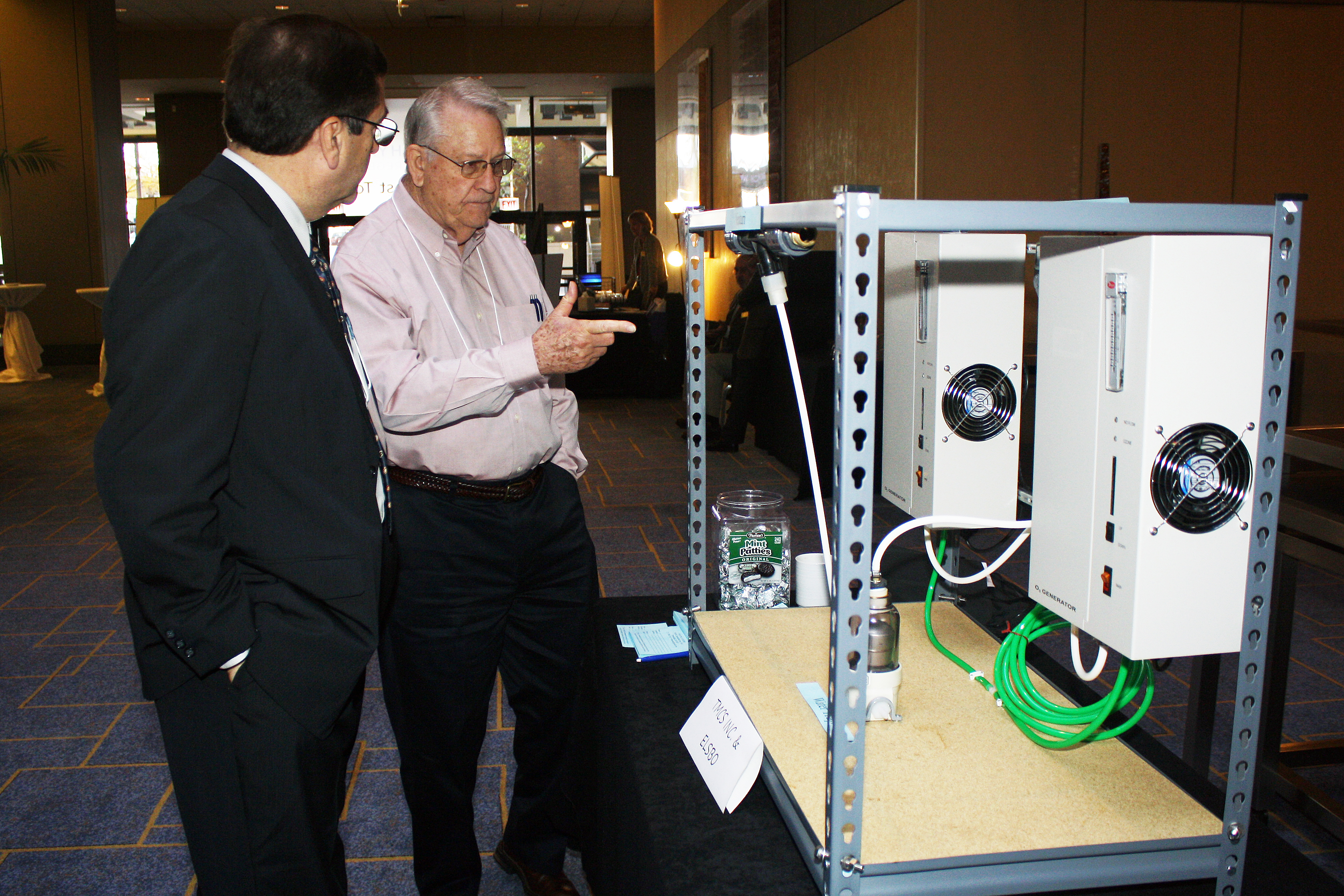 attendees looking at a display of small heating systems