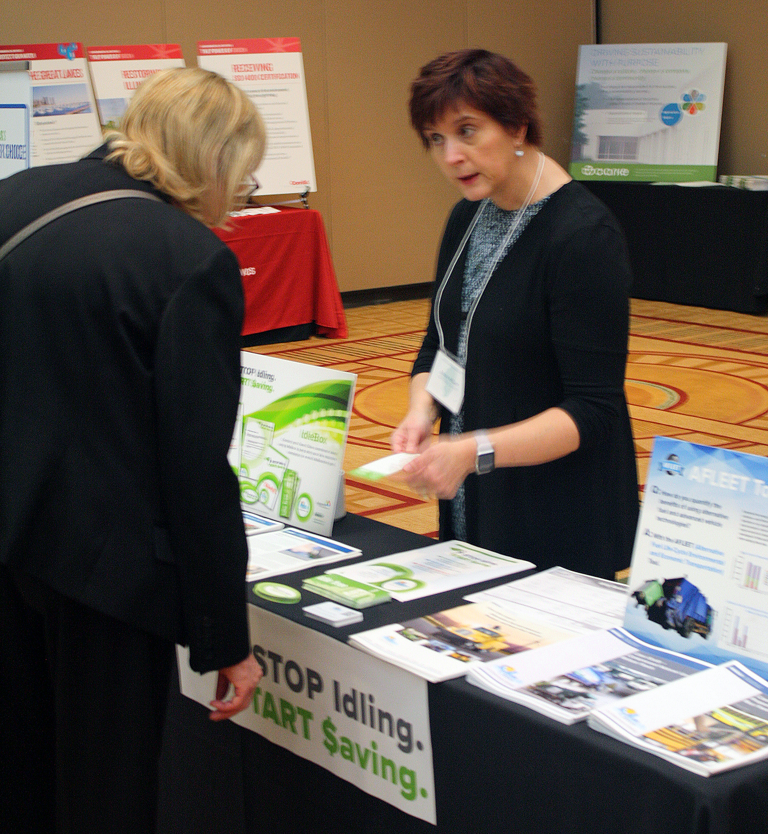 attendee speaking with a representative at a display table