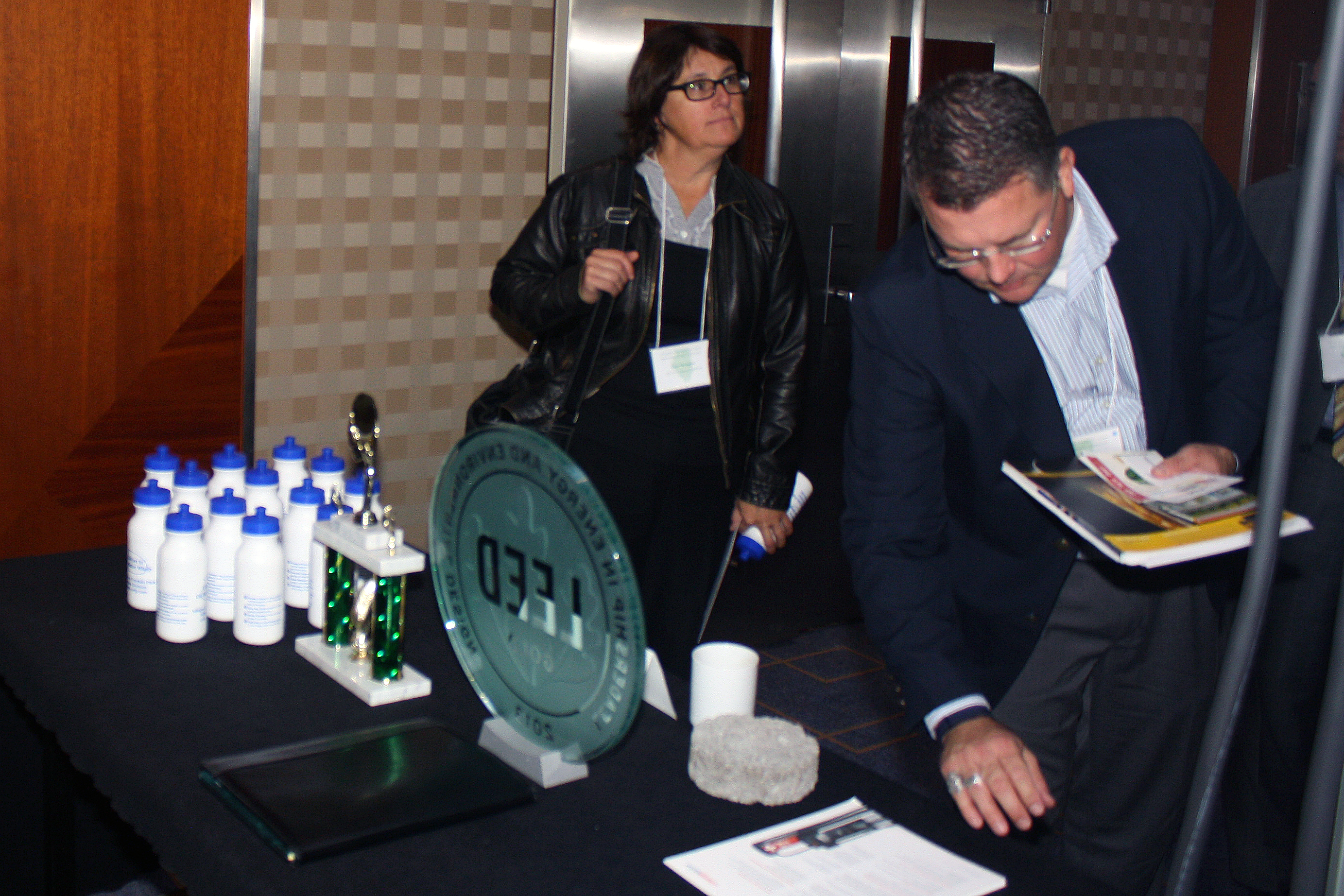 attendees taking pamphlets from a display table with a LEED cerdifed plaque