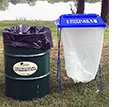 trash can and recycling bag on a stand next to each other in a park