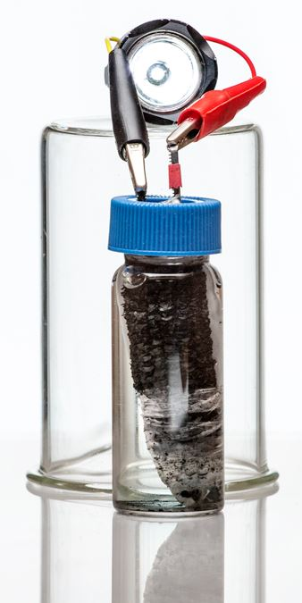 corn cob biochar chunk is in a week acid solution inside a capped jar. electrodes come out of the cap and are connected to a lit LED light.
