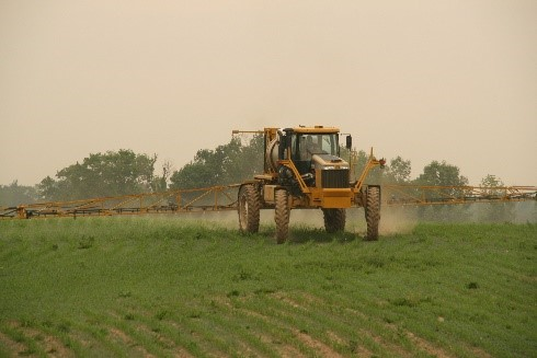 tractor spraying chemicals on a field