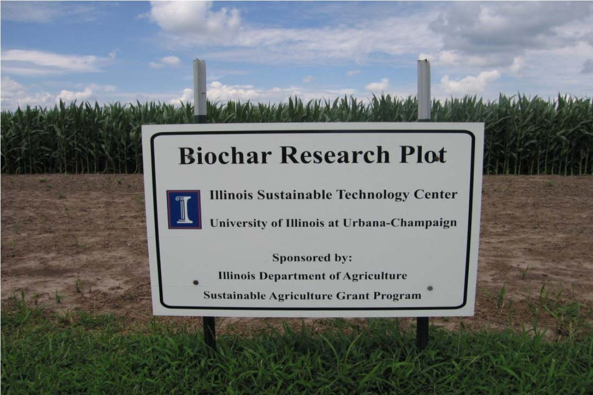 Biochar Research Plot sign at the field site with green corn in the background