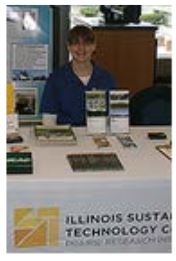 Beth Meschewski posing sitting behind the ISTC display table