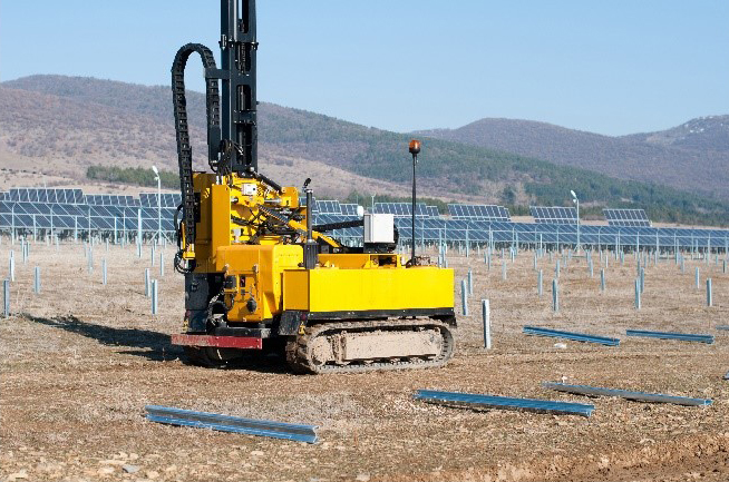 solar panel field being installed. tractor equipment pounding posts into the ground. posts hold the solar panels up.