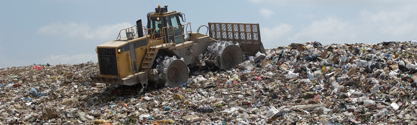 tractor pushing trash around on a gigantic trash pile in a landfill