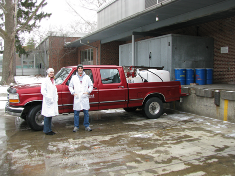 red truck with large tanks in the back of the truck and two students in lab coats standing next to the truck